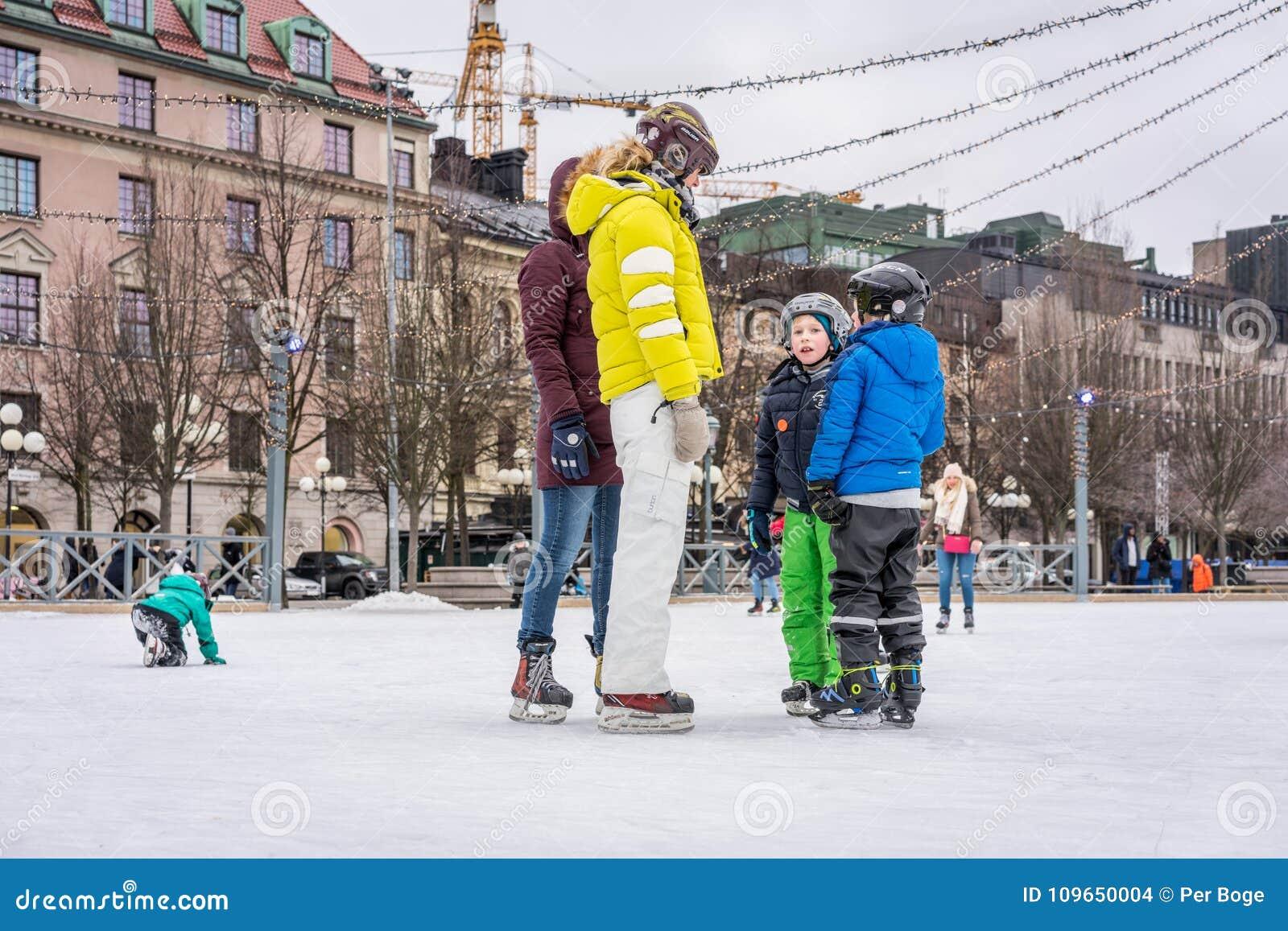 Två kvinna och barn som utomhus åker skridskor på en offentlig skridskoåkningisbana i staden