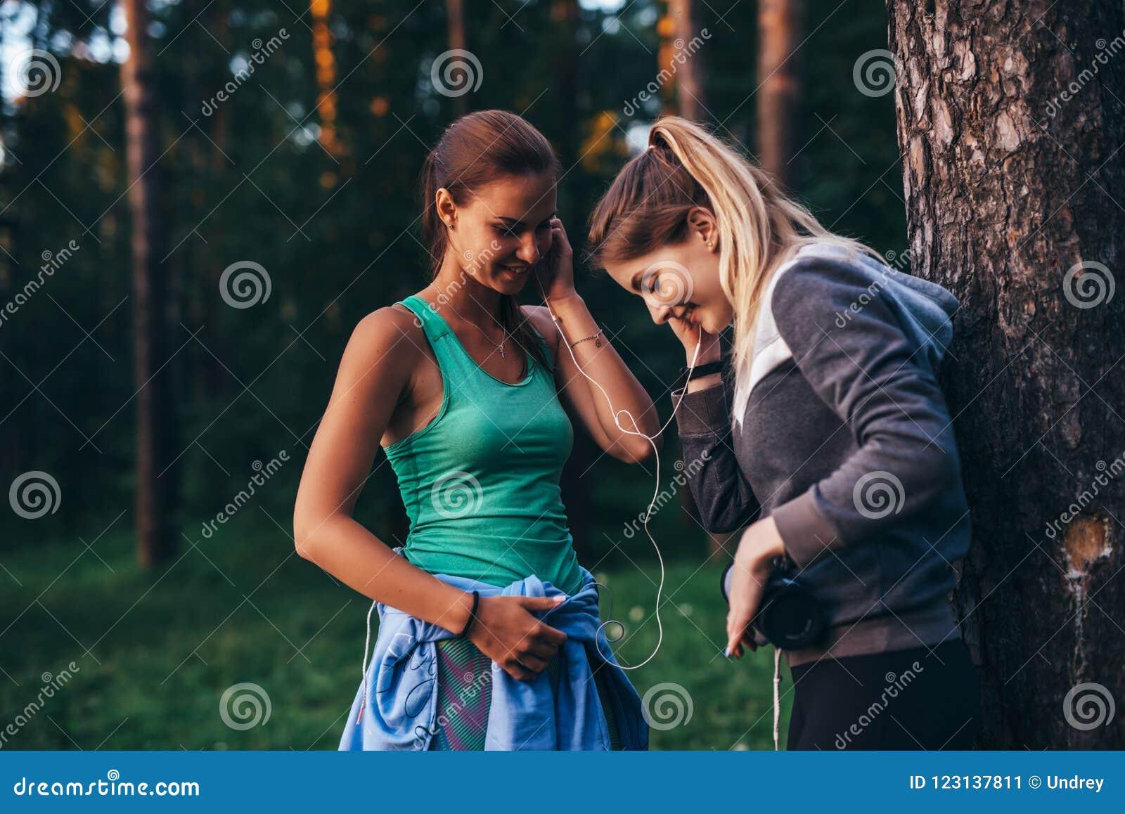 Två kvinnliga löpare som kopplar av efter genomkörareanseende nära trädet som in talar, parkerar