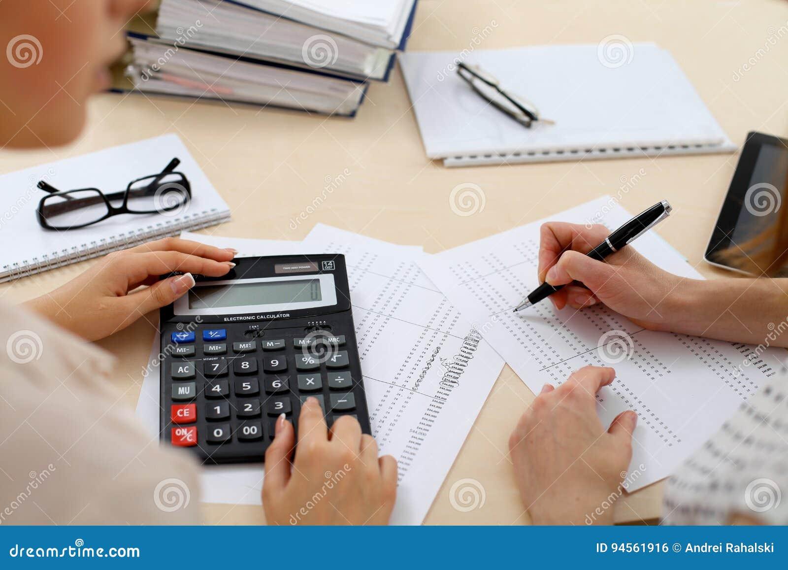 Två kvinnliga revisorer som räknar på räknemaskininkomst för avslutning för skattform, räcker closeupen Skattemyndigheten