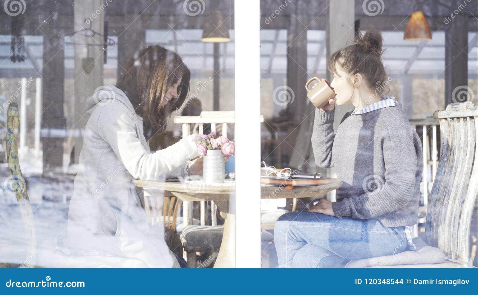 Två kvinnliga vänner som möter i ett kafé för att tala