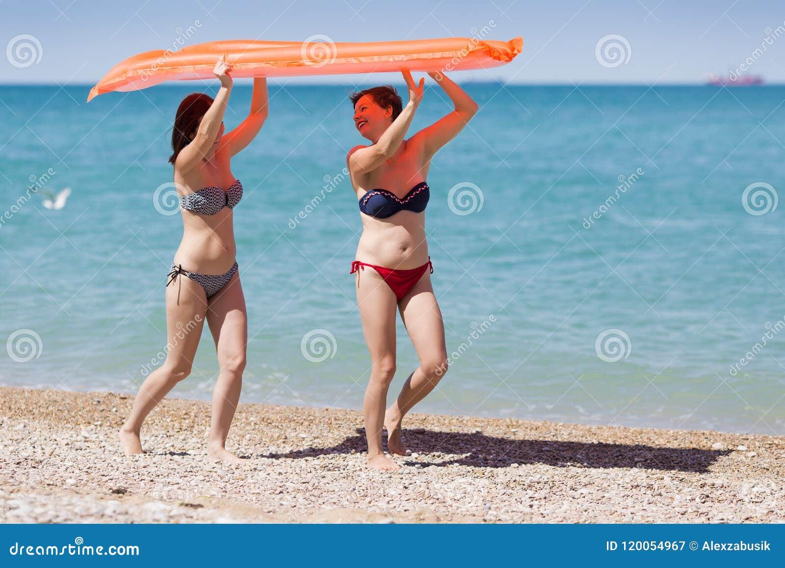 Två kvinnor i baddräkter som bär den uppblåsbara flotten över deras huvud