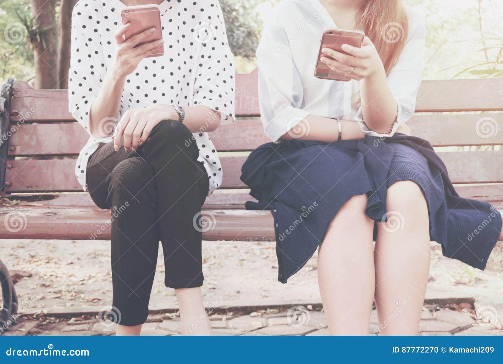 Två kvinnor i disinterestögonblick med smarta telefoner i det utomhus-, begrepp av förhållandeapati och användany teknik och smar