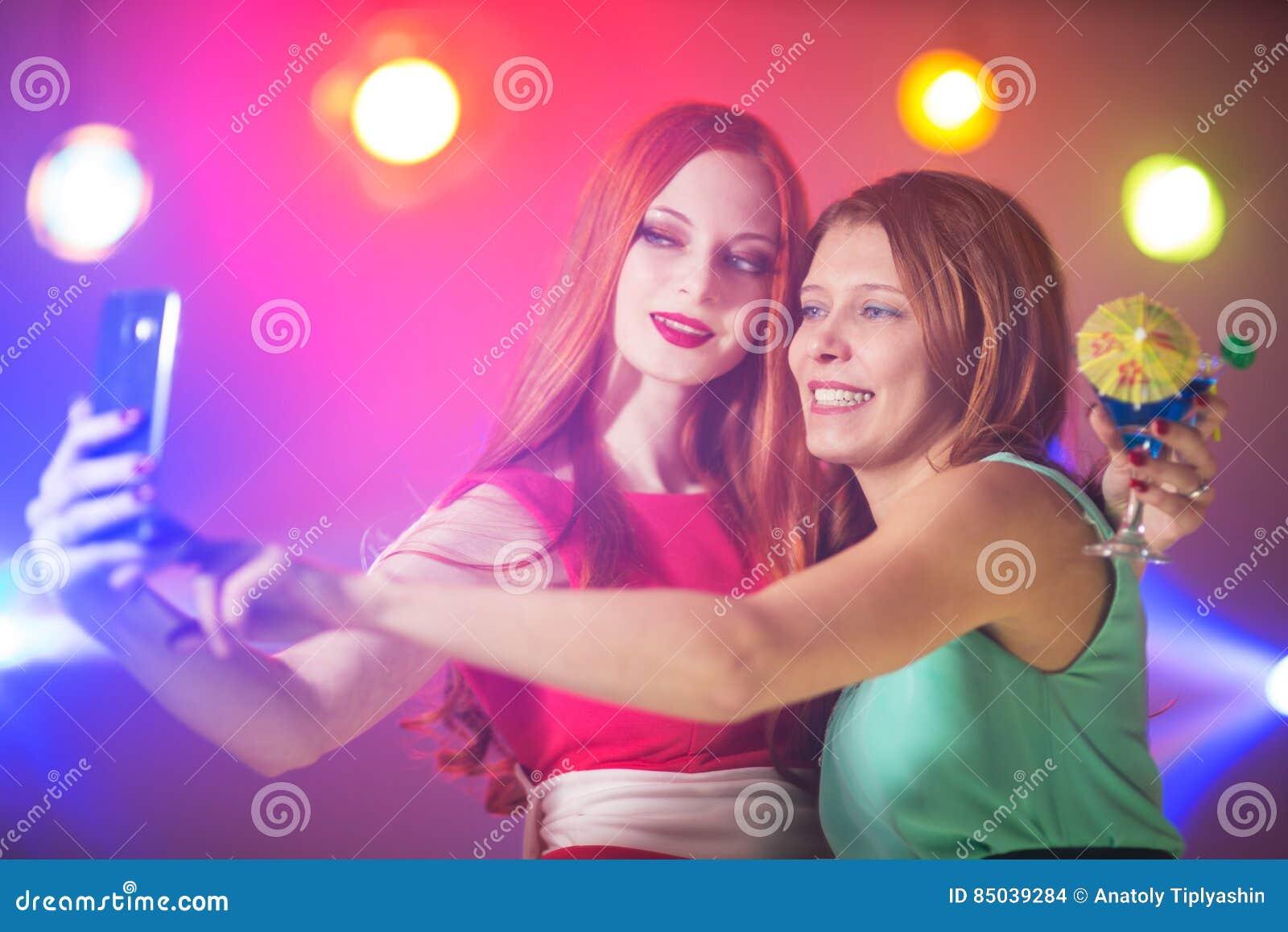 Två kvinnor i en nattklubb under strålkastaren med en coctail in