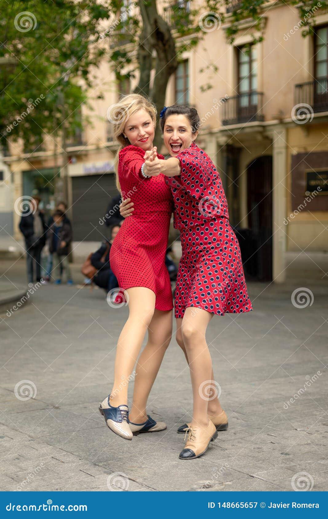 Två kvinnor i röd dans omfamnade lyckligt i gatan
