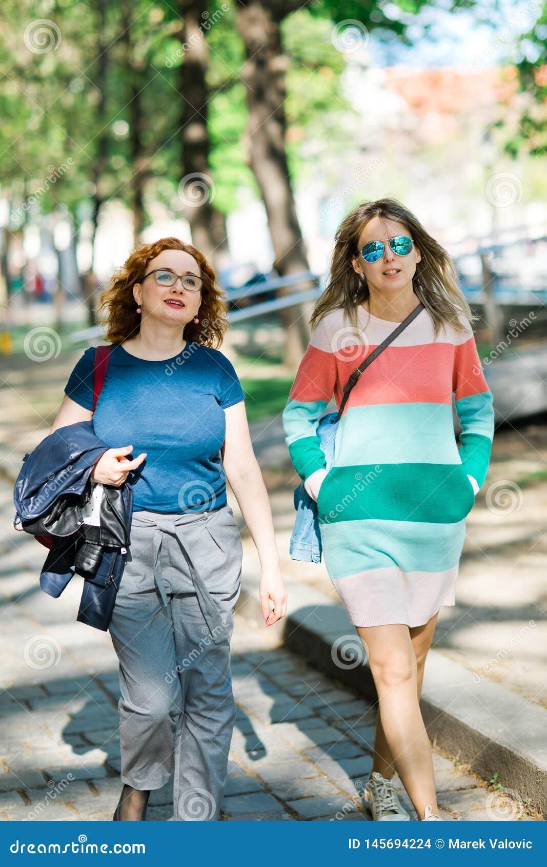 Två kvinnor i staden som tillsammans går - kvinnan med färgmellanrum på klänningen