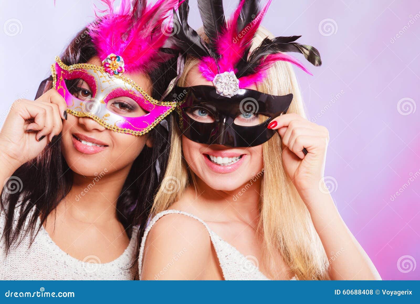 Två kvinnor med venetian maskeringar för karneval