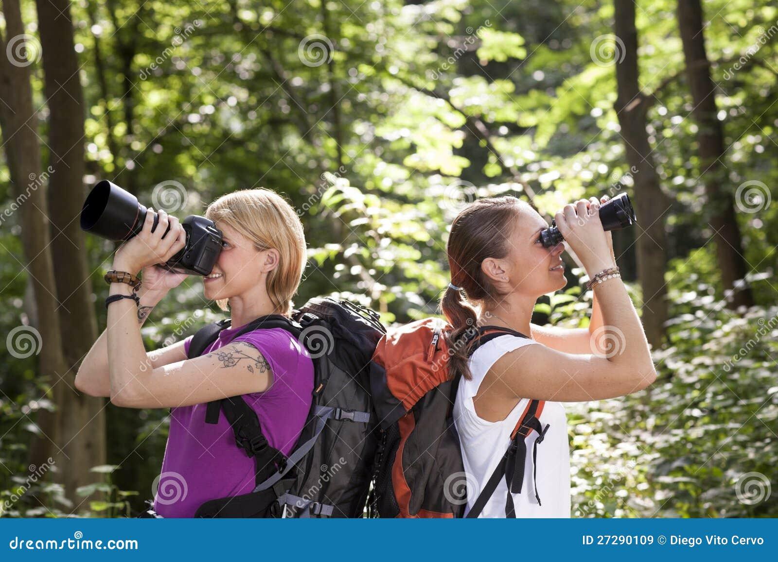 Två kvinnor som fotvandrar och ser med kikare