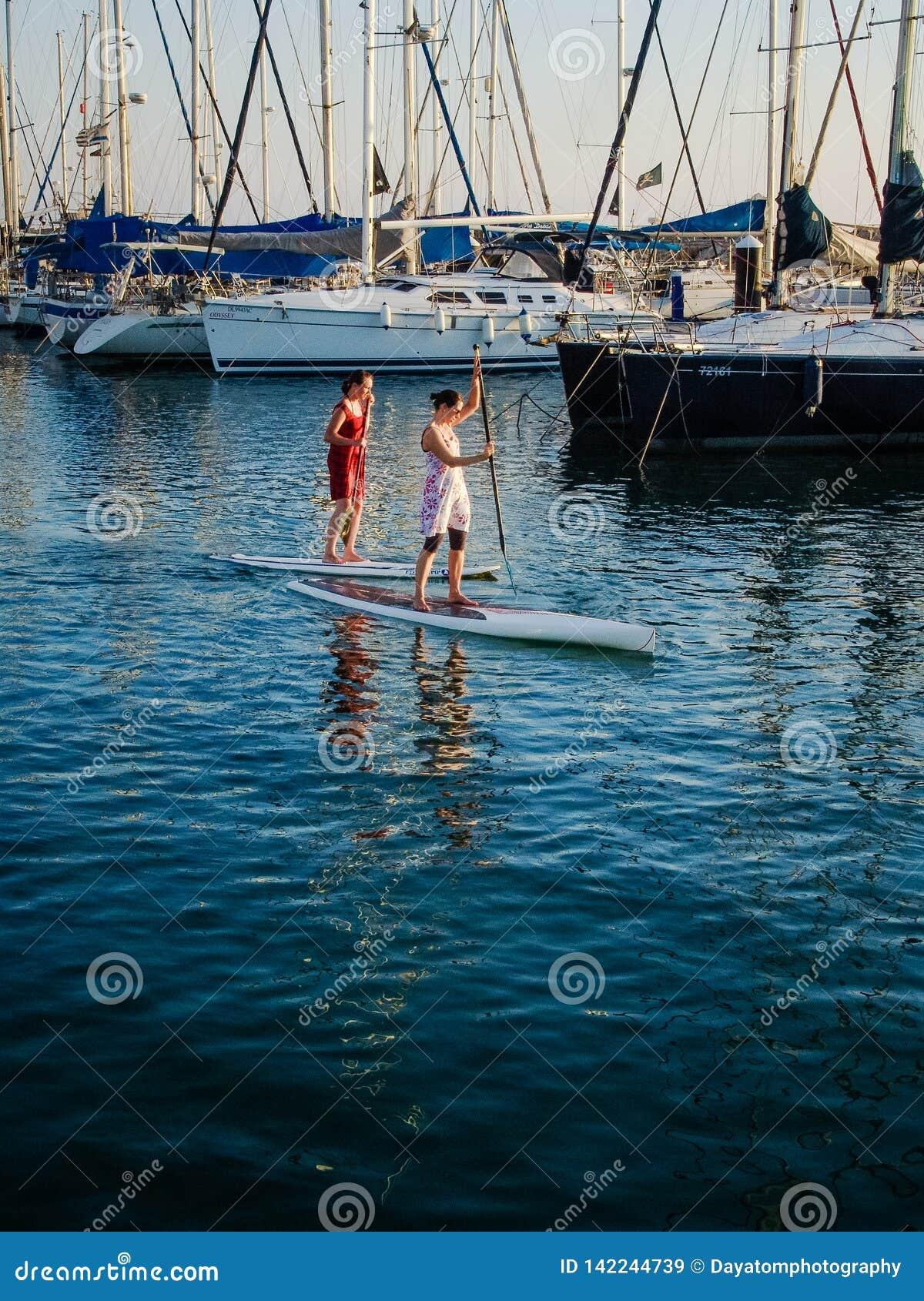 Två kvinnor som framme surfar på sups i Tel Aviv port av härbärgerade fartyg och yachter