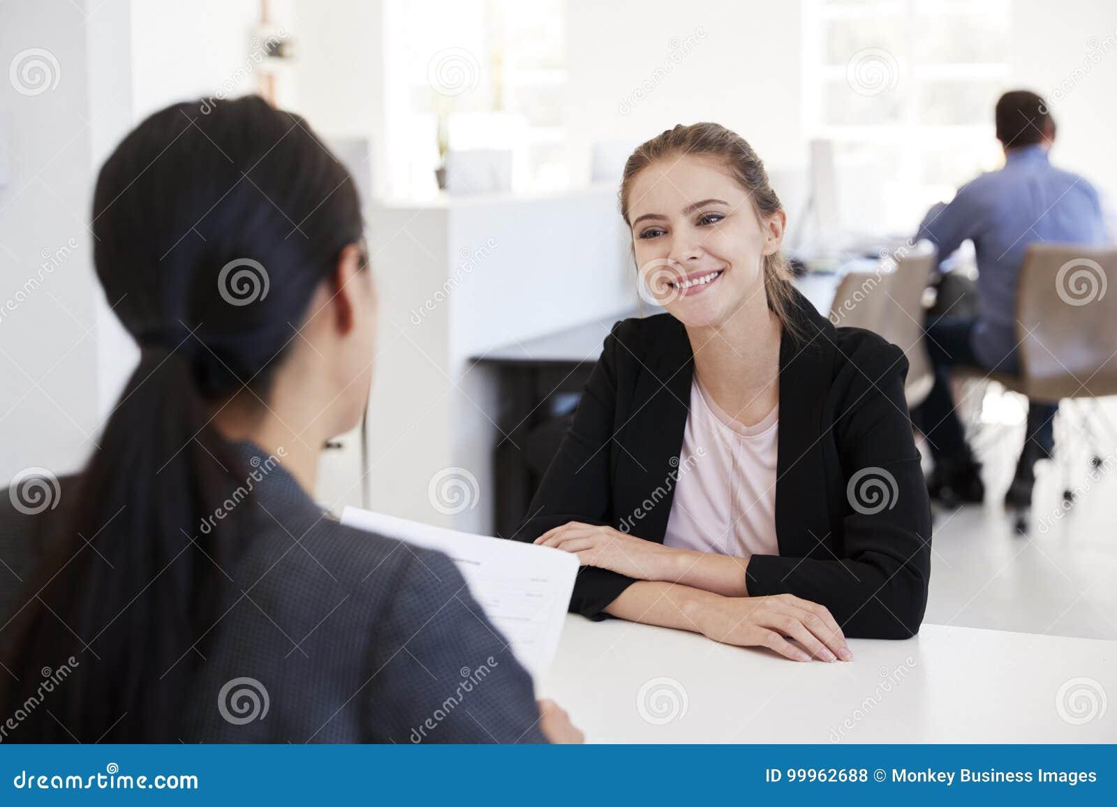 Två kvinnor som sitter på en intervju i ett öppet plankontor
