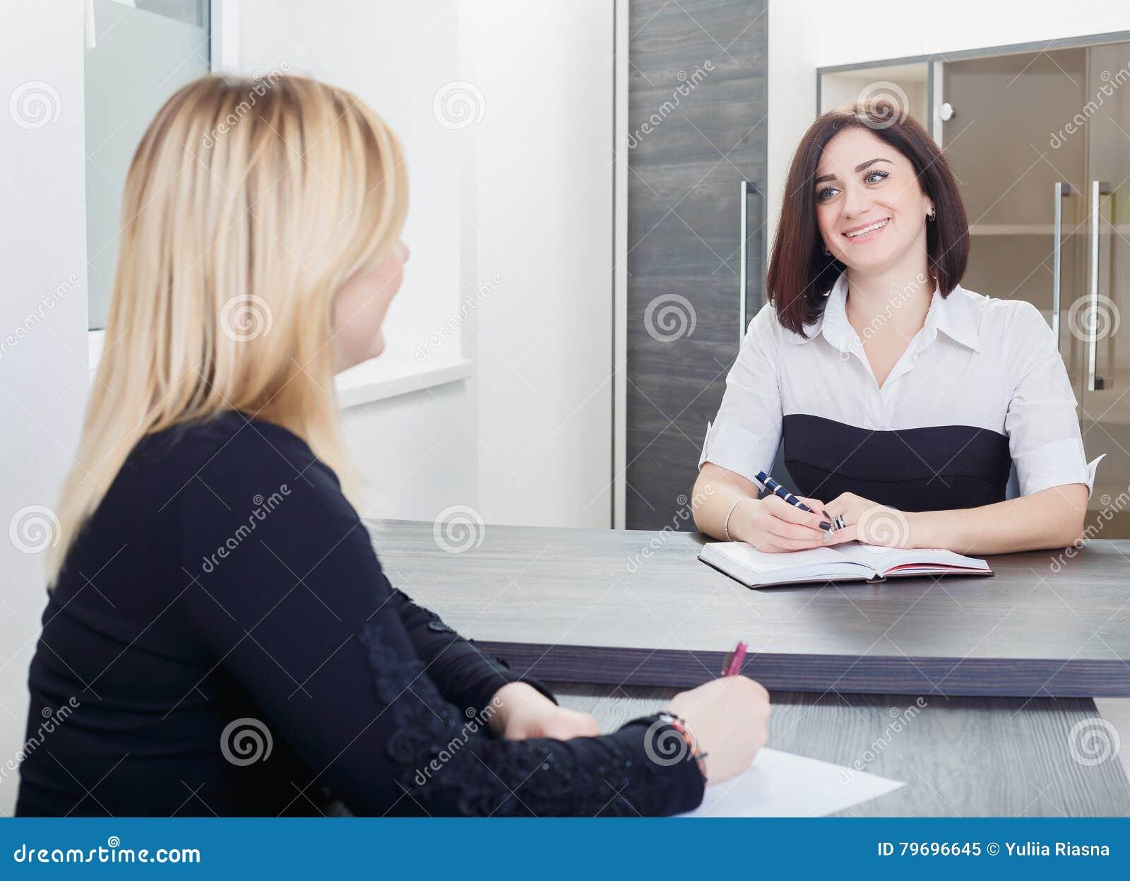 Två kvinnor som sitter på en tabell i kontoret Blondin och brunett på jobbintervju eller möte