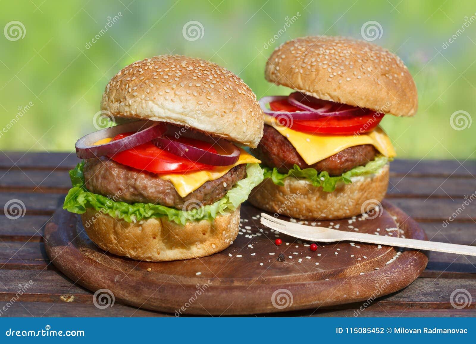 Två läckra hamburgare på träbräde
