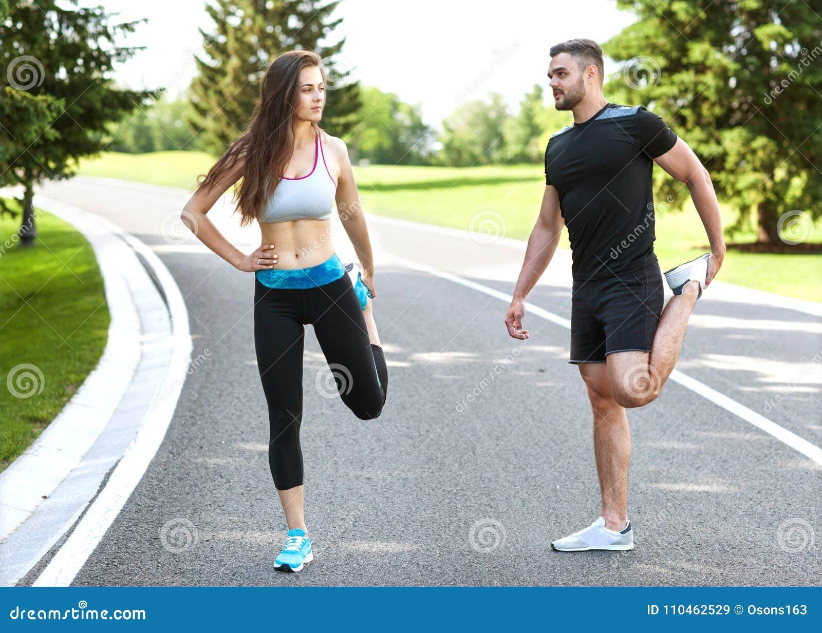 Två löpare som utomhus sprintar - Sportive folk som utbildar i a