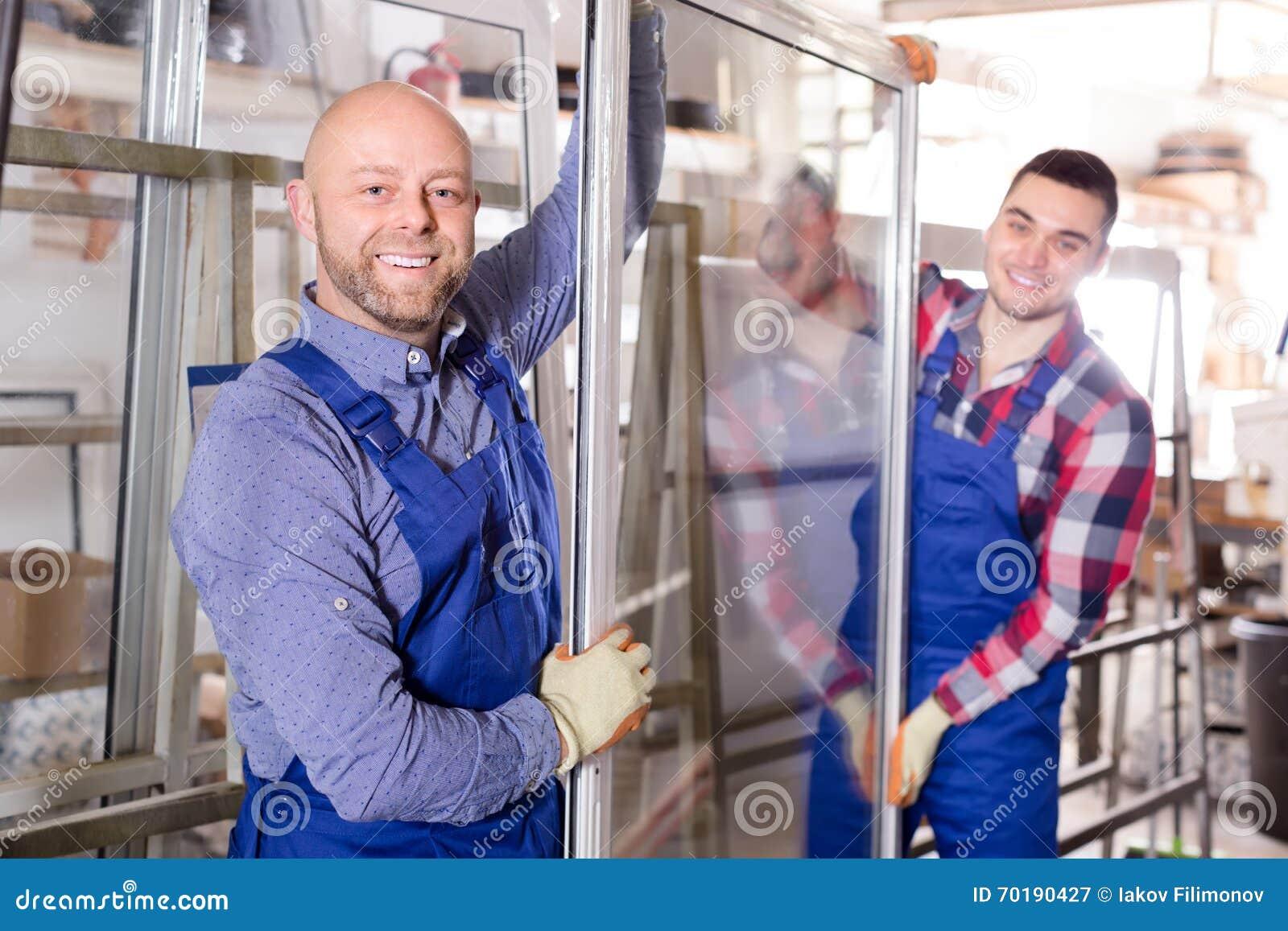 Två le arbetare på fabriken