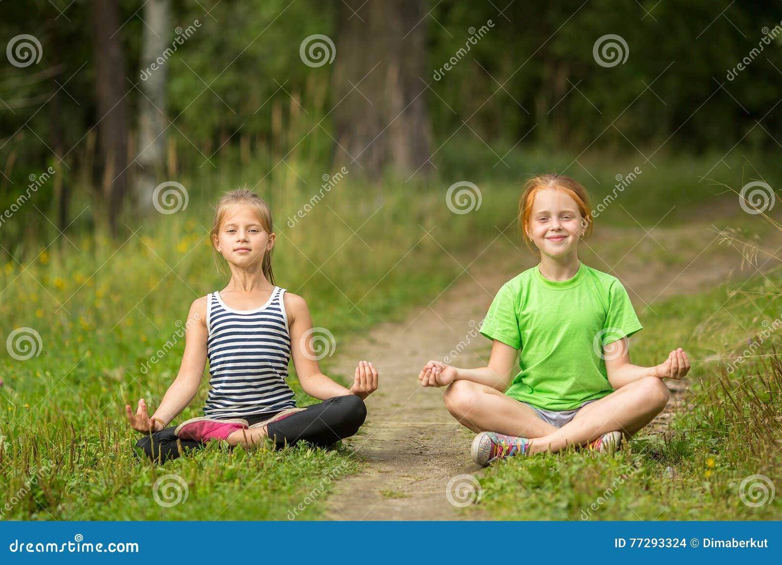 Två lilla gulliga yogaflickor som sitter i den Lotus positionen