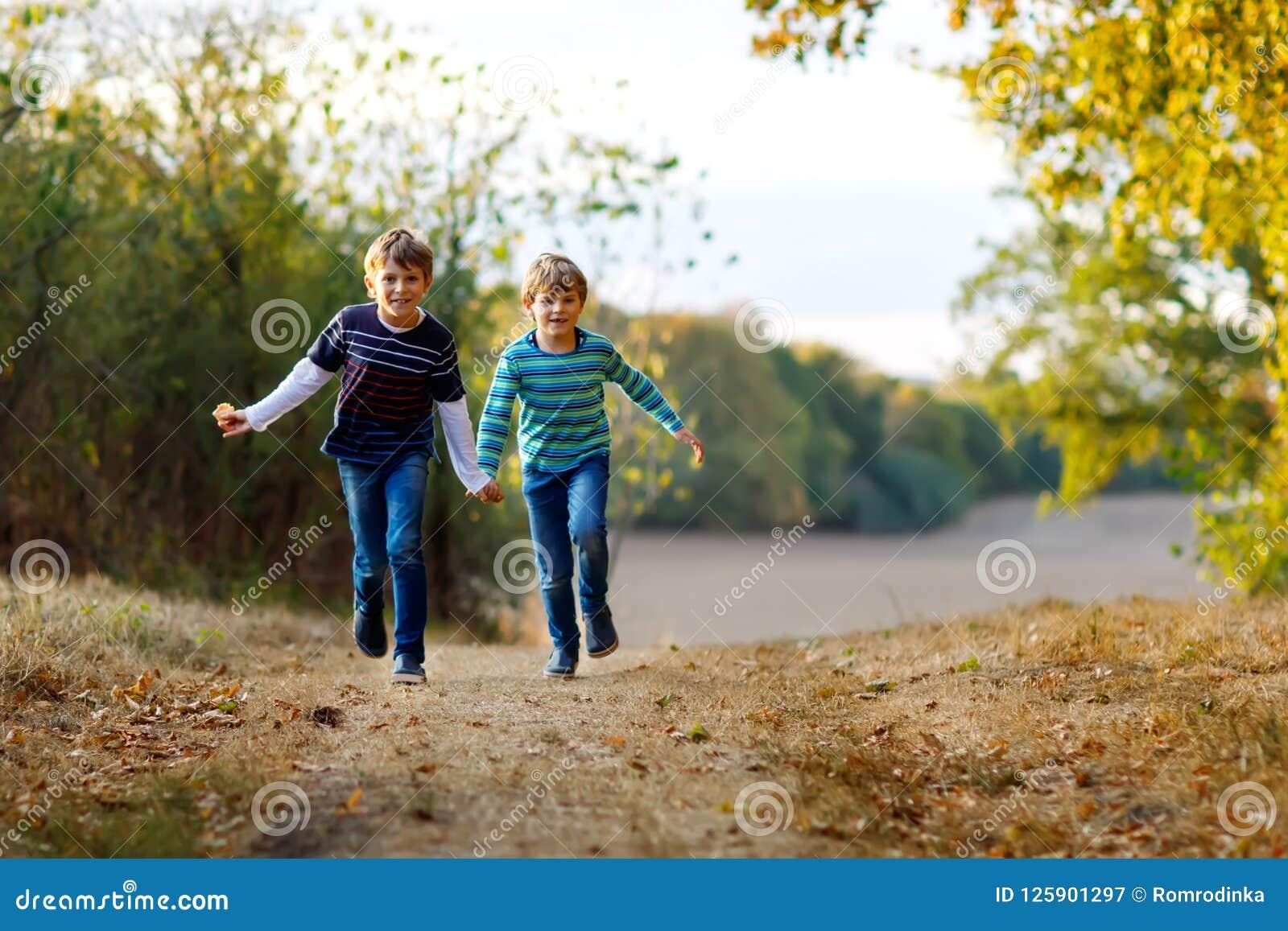 Två lilla skolaungepojkar som kör och hoppar i barn, bästa vän och syskon för skog som lyckliga har gyckel på varmt