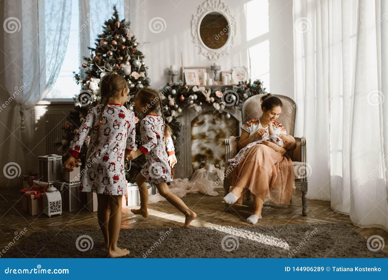 Två lilla systrar i pyjamas som har roliga det nya årets träd med gåvor i det ljusa hemtrevliga rummet och deras moder, sitte