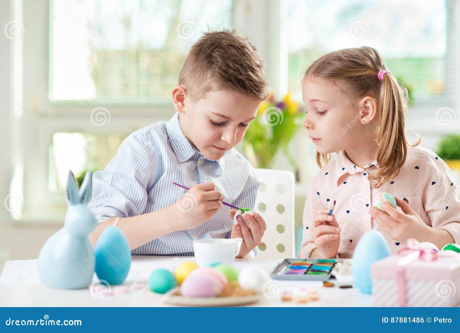 Två lyckliga barn som har gyckel under målningägg för easter in