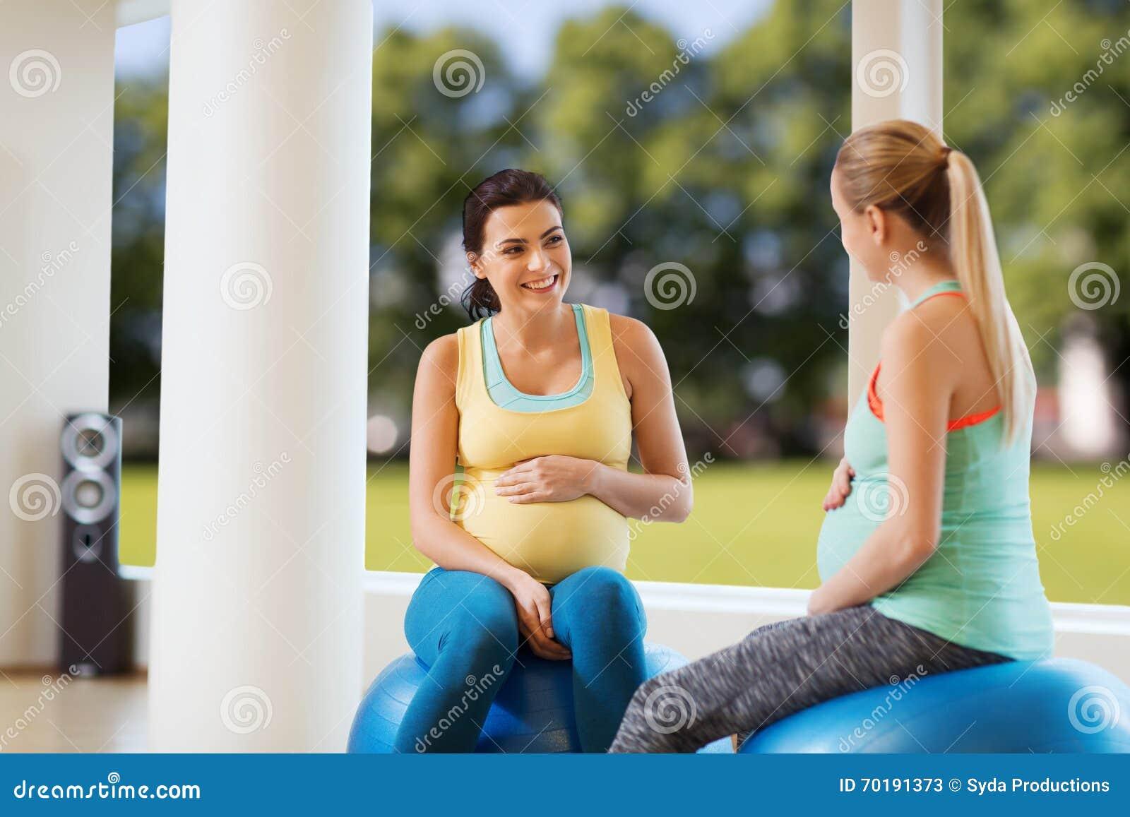 Två lyckliga gravida kvinnor som sitter på bollar i idrottshall
