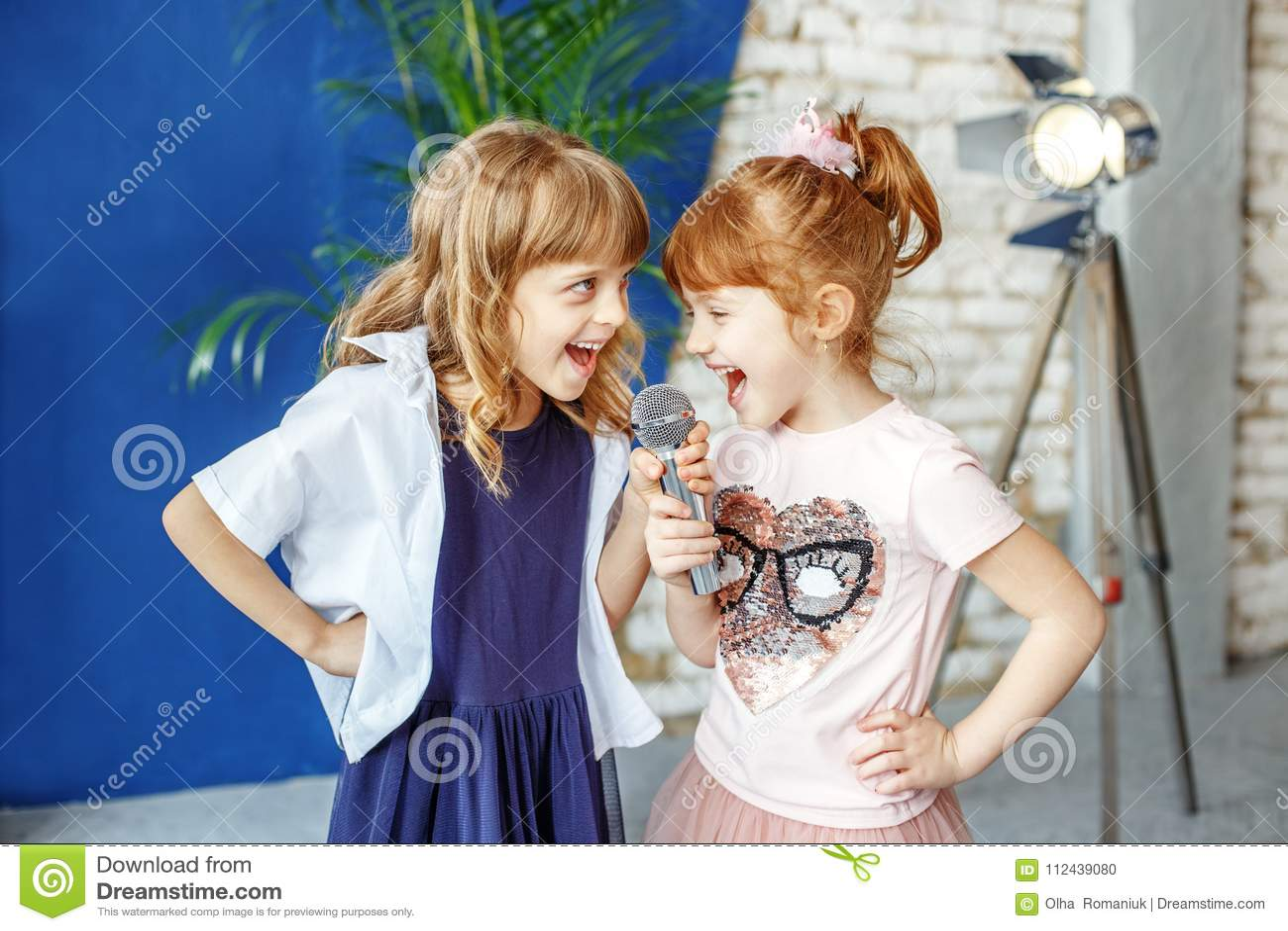 Två lyckliga lilla barn sjunger en sång i karaoke Begreppet är