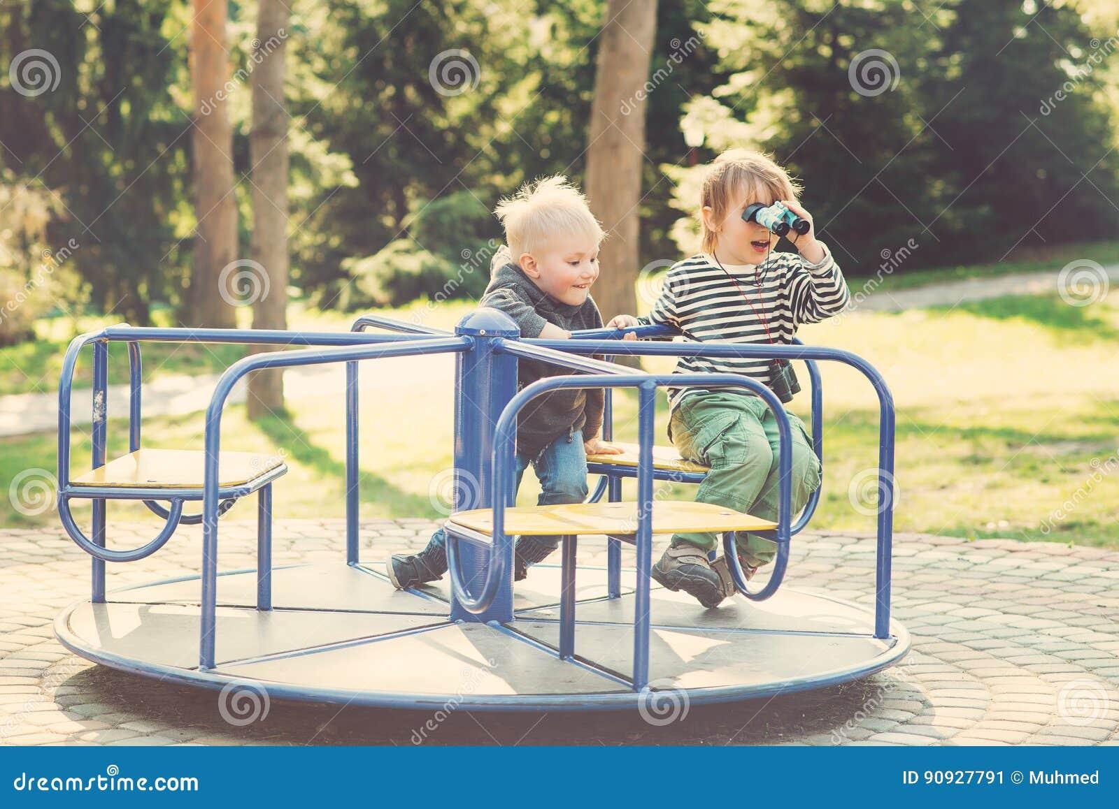 Två lyckliga pojkar som spelar på lekplats i en parkera tonat
