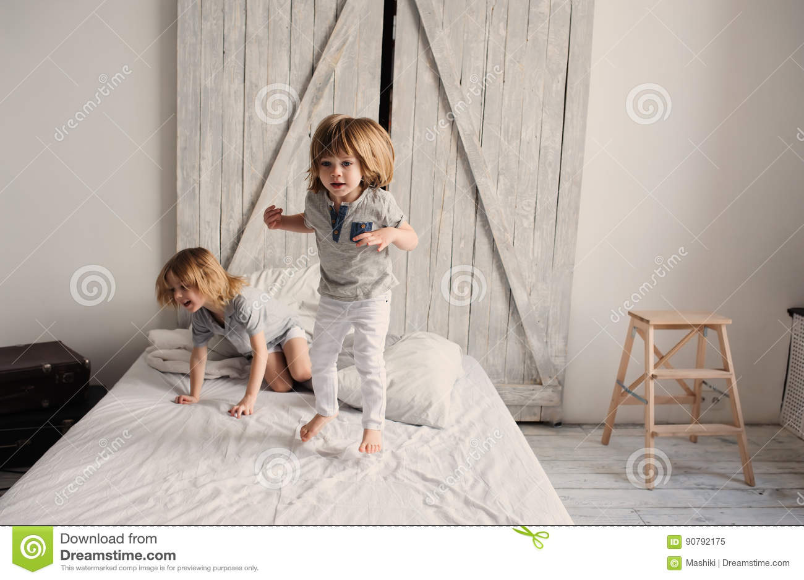 Två lyckliga siblingpojkar som tillsammans hemma spelar på säng