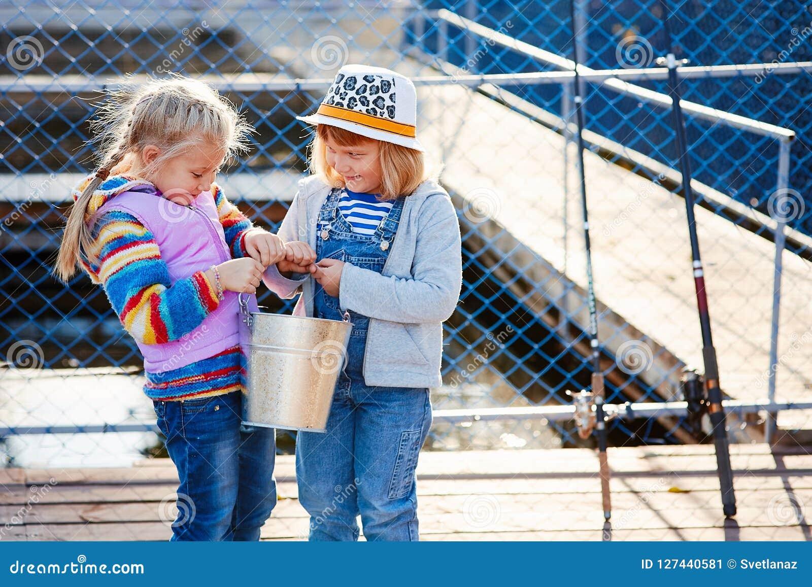 Två lyckliga skratta barn med metspön och en hink på a