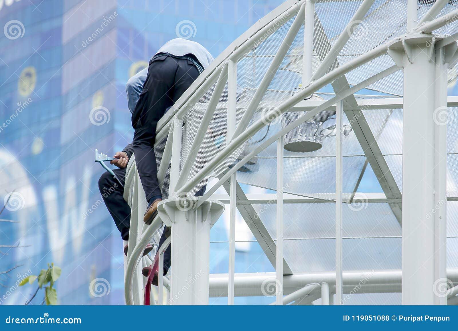Två män arbetar på ett högt tak