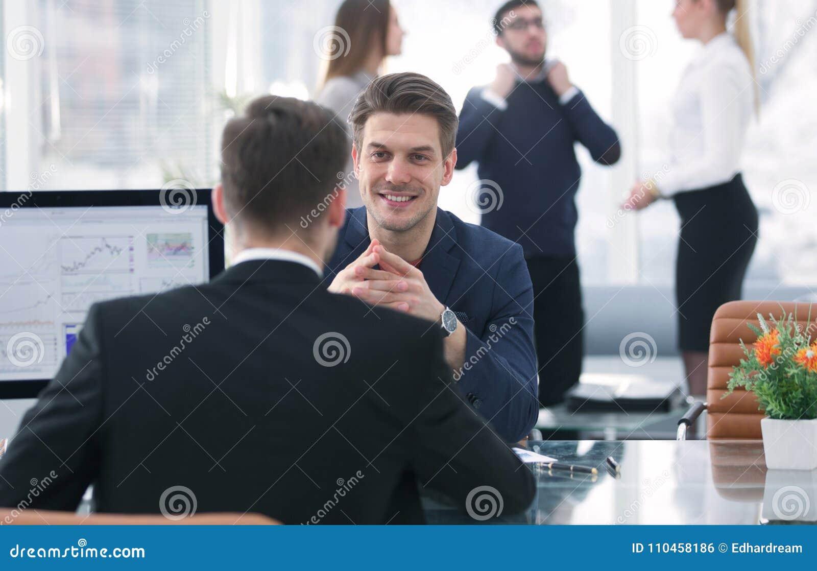 Två män diskuterar tillväxten av företaget som ser resninggrafen på en datorskärm