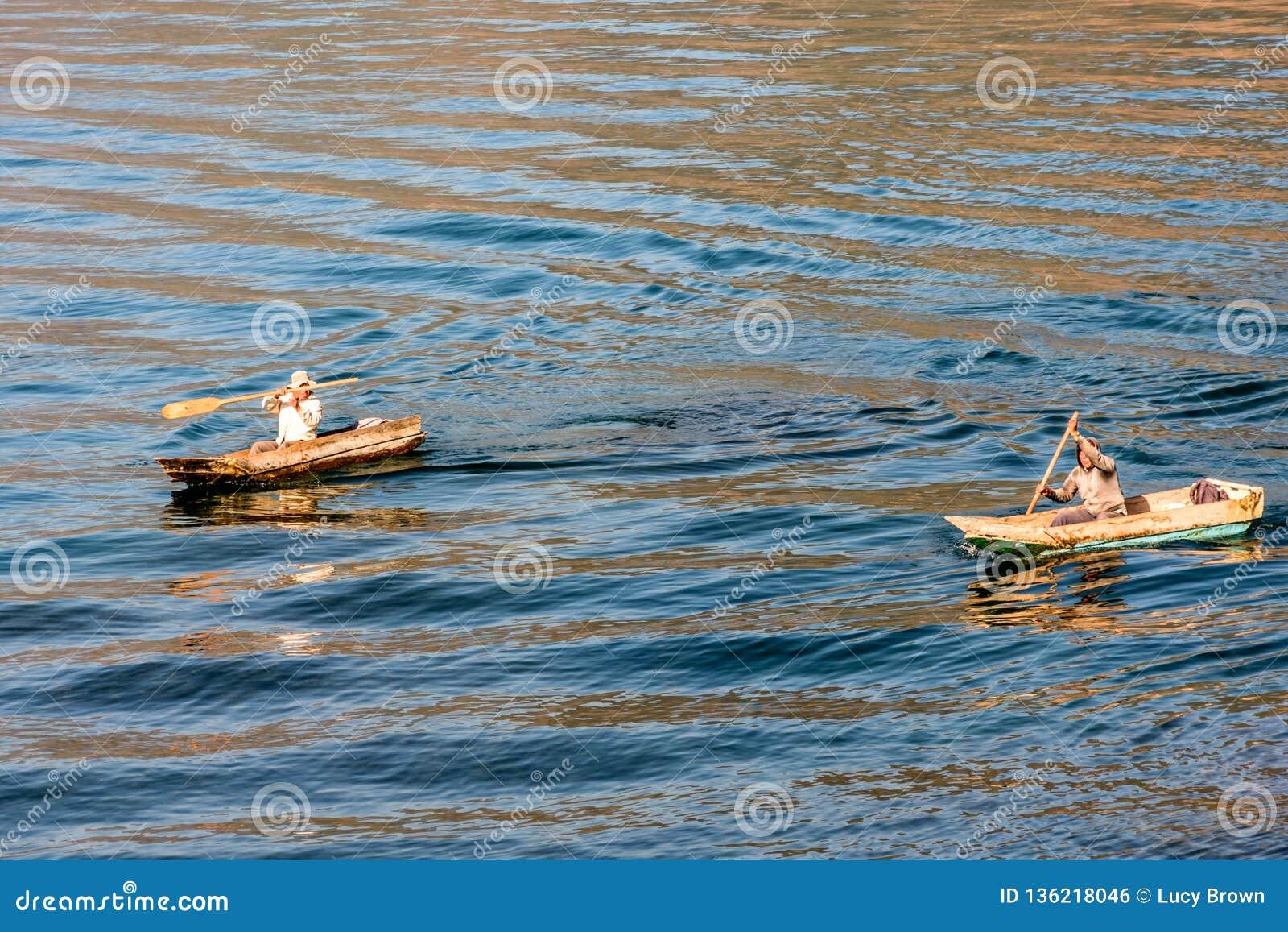 Två män i dugoutkanoter på sjön Atitlan, Guatemala