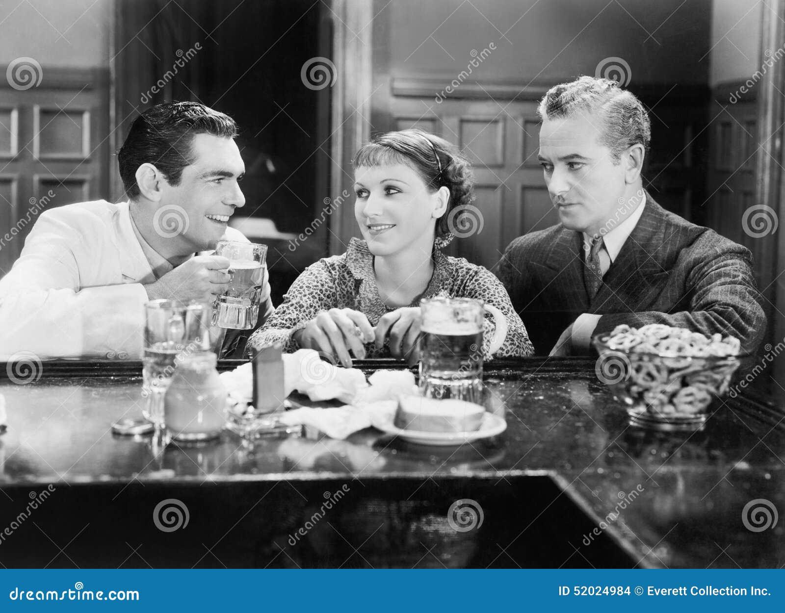 Två män och ett kvinnasammanträde på en stång som dricker öl (alla visade personer inte är längre uppehälle, och inget gods finns