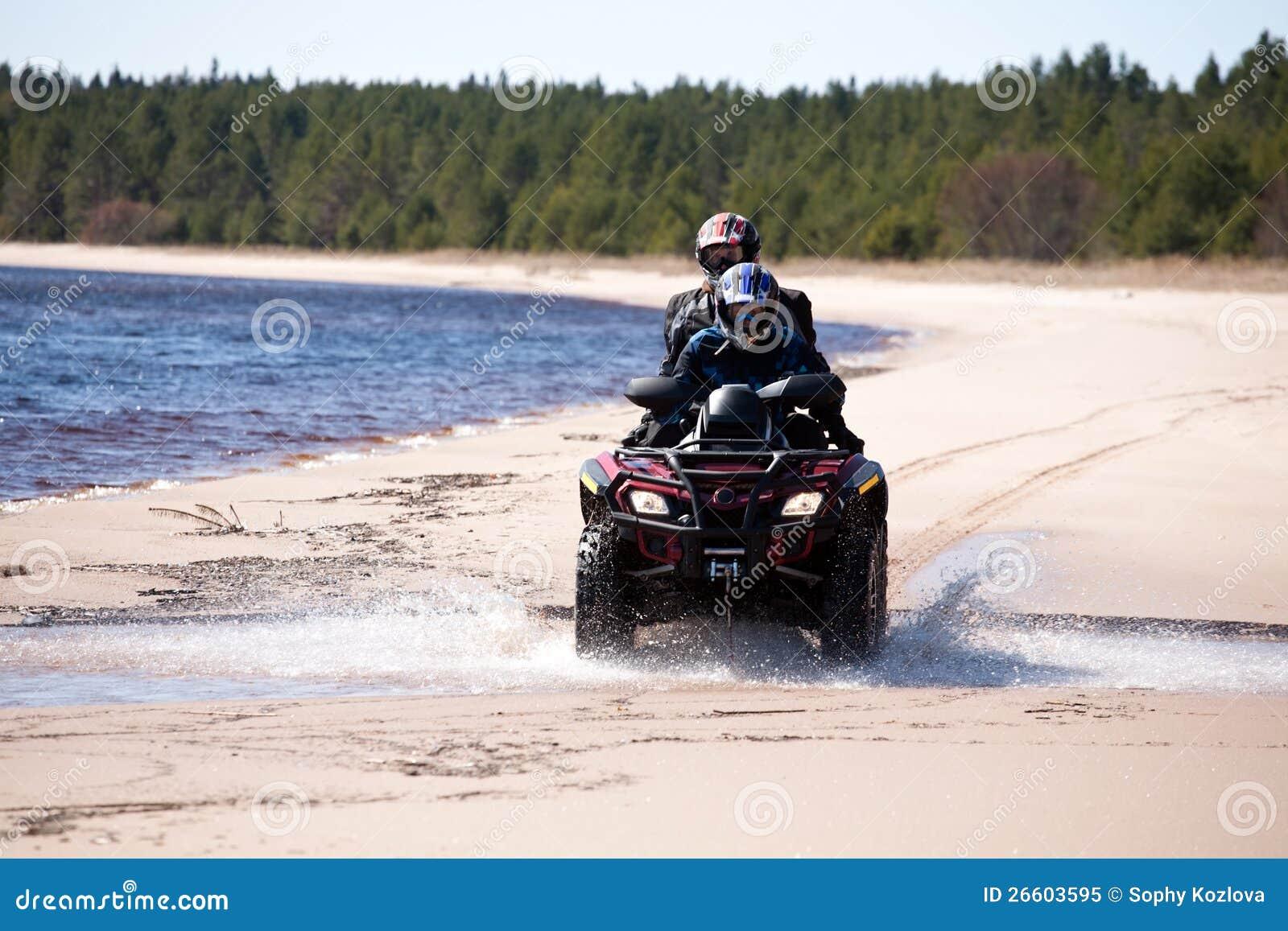 Två män som rider det all-terrain medlet