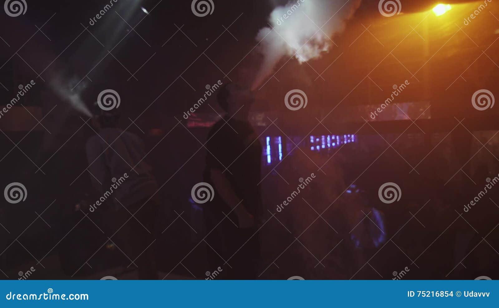 Två män utandas ånga från den elektroniska cigaretten i nattklubb challenge folk lager videofilmer