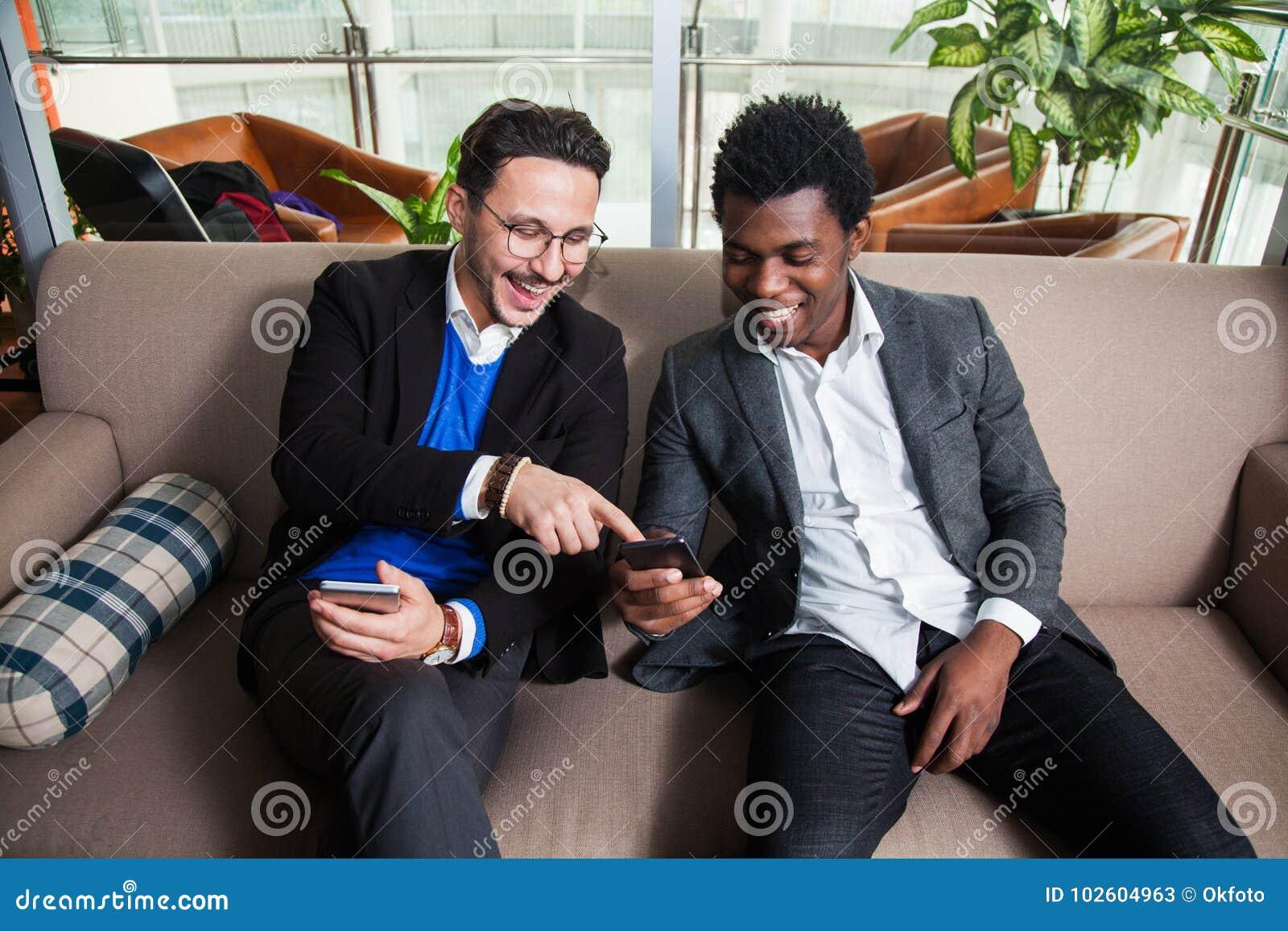 Två mångkulturella män sitter på soffa-, leende- och hållmobiltelefoner