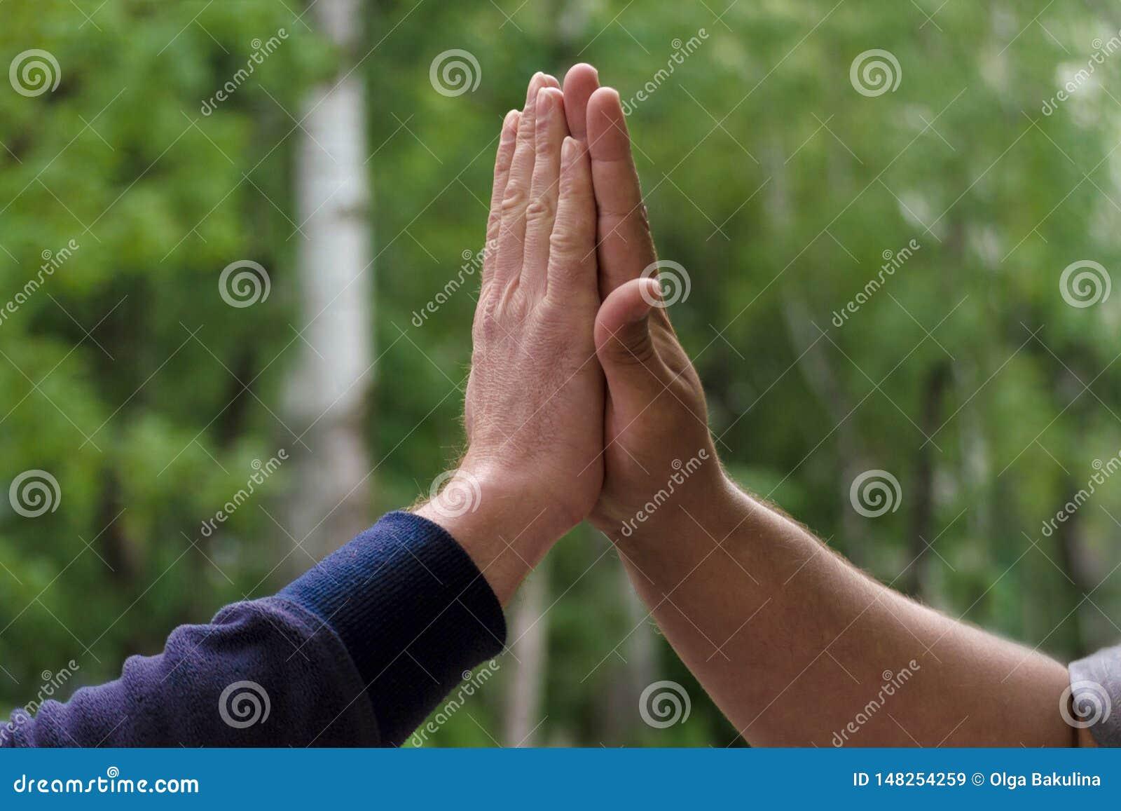 Två mötande hälsning för män höga fem Begrepp av lyckliga och lyckade affärskollegor som ger högt fem Nära övre sikt på gräsplan
