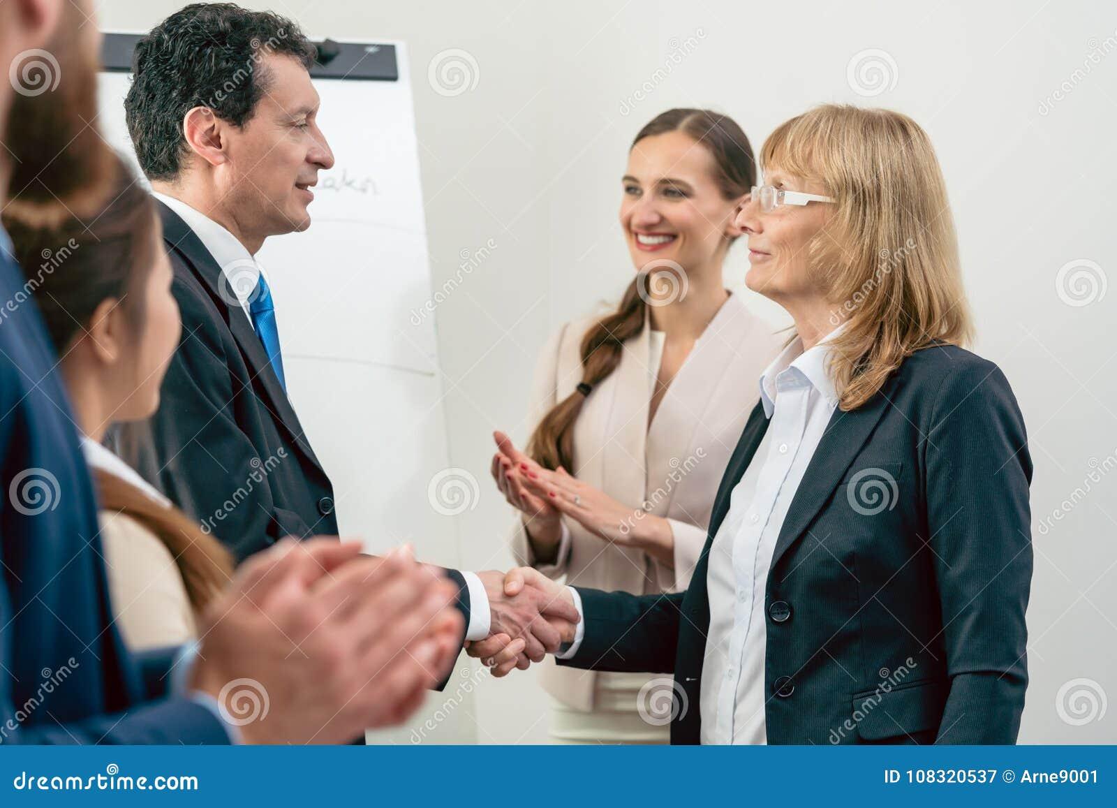 Två medelåldersa affärsbundsförvanter som ler, medan skaka händer