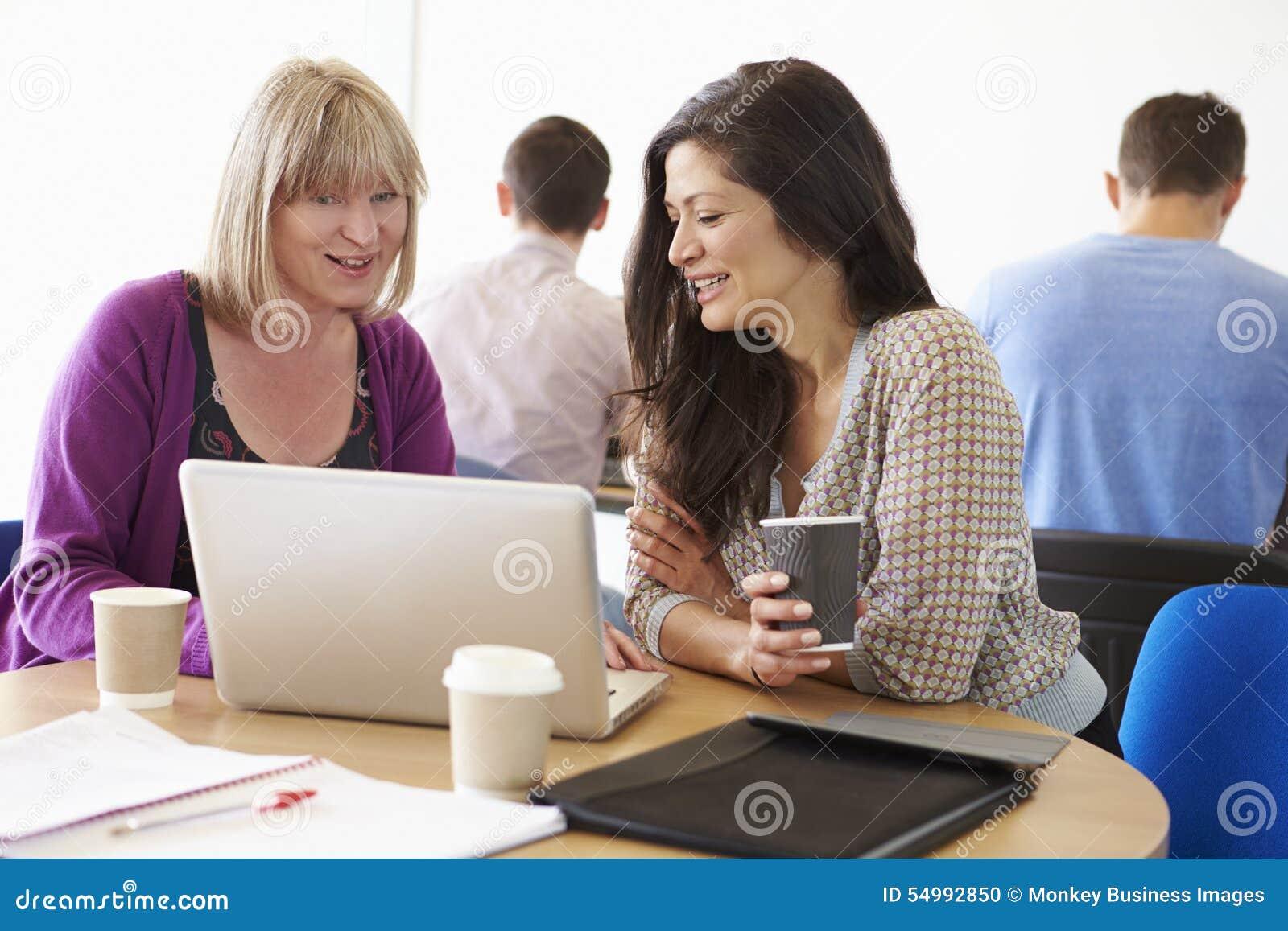 Två mogna studenter för kvinnlig som arbetar tillsammans genom att använda bärbara datorn