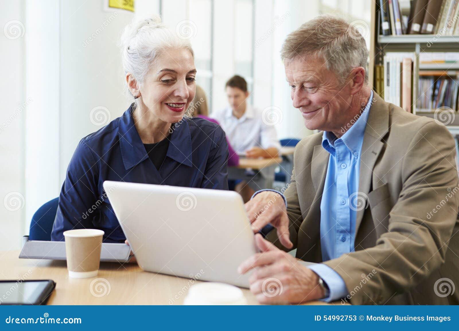 Två mogna studenter som tillsammans arbetar i arkiv genom att använda bärbara datorn