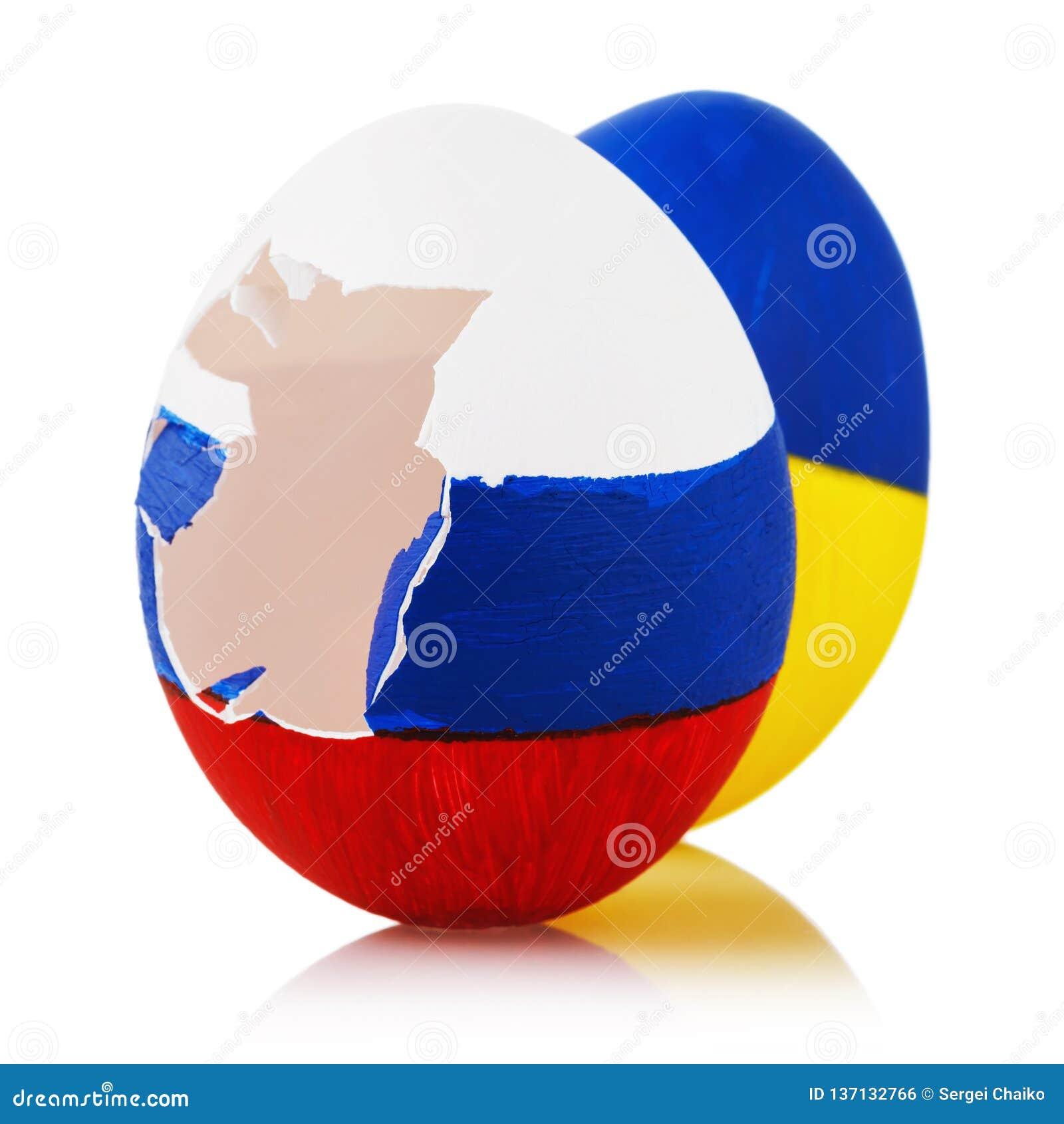 Två påskägg som målas i färg av flaggor av Ryssland och Ukraina på vit bakgrund, closeup