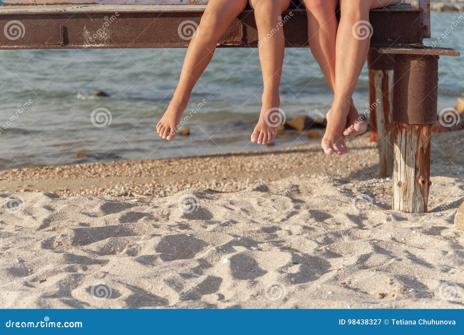 Två par av ben som dinglar över strandsanden