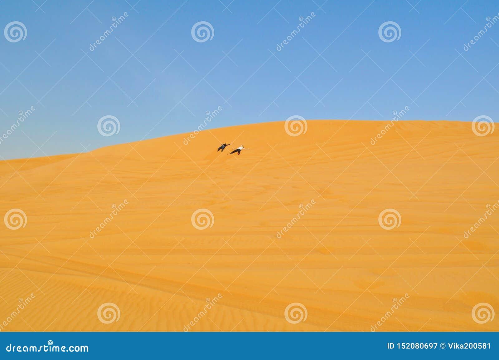 Två personer korsar öknen Aktiv ferie i Dubai Gränslös sandig öken