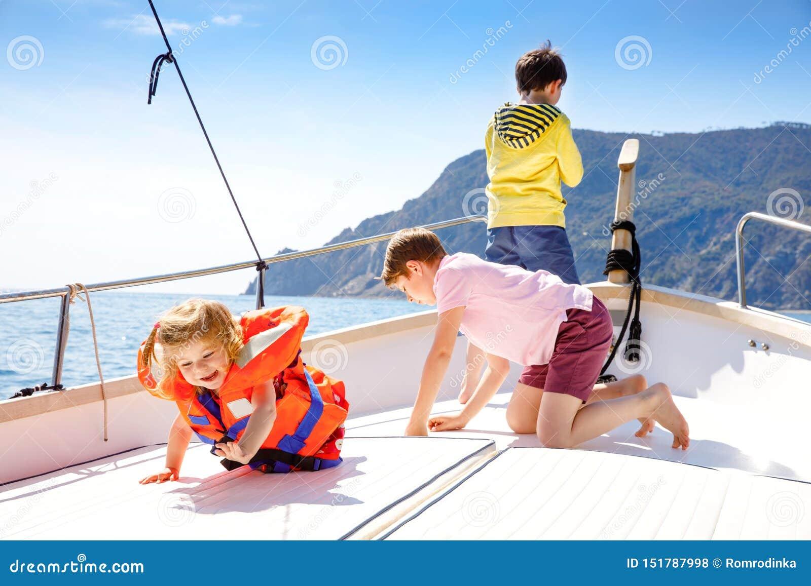 Två pojkar för liten unge och litet barnflicka som tycker om segelbåttur Familjsemestrar p? havet eller havet p? solig dag Barn