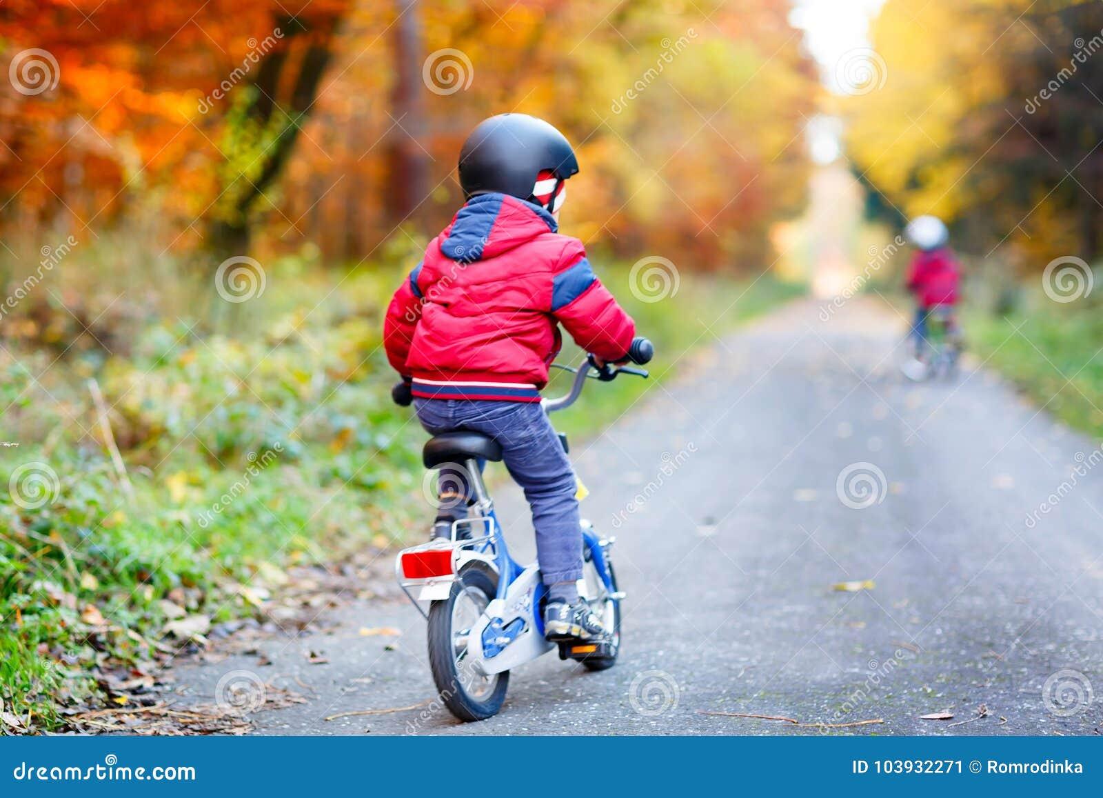 Två pojkar för liten unge som cyklar med cyklar i hösten Forest Park i färgrik kläder