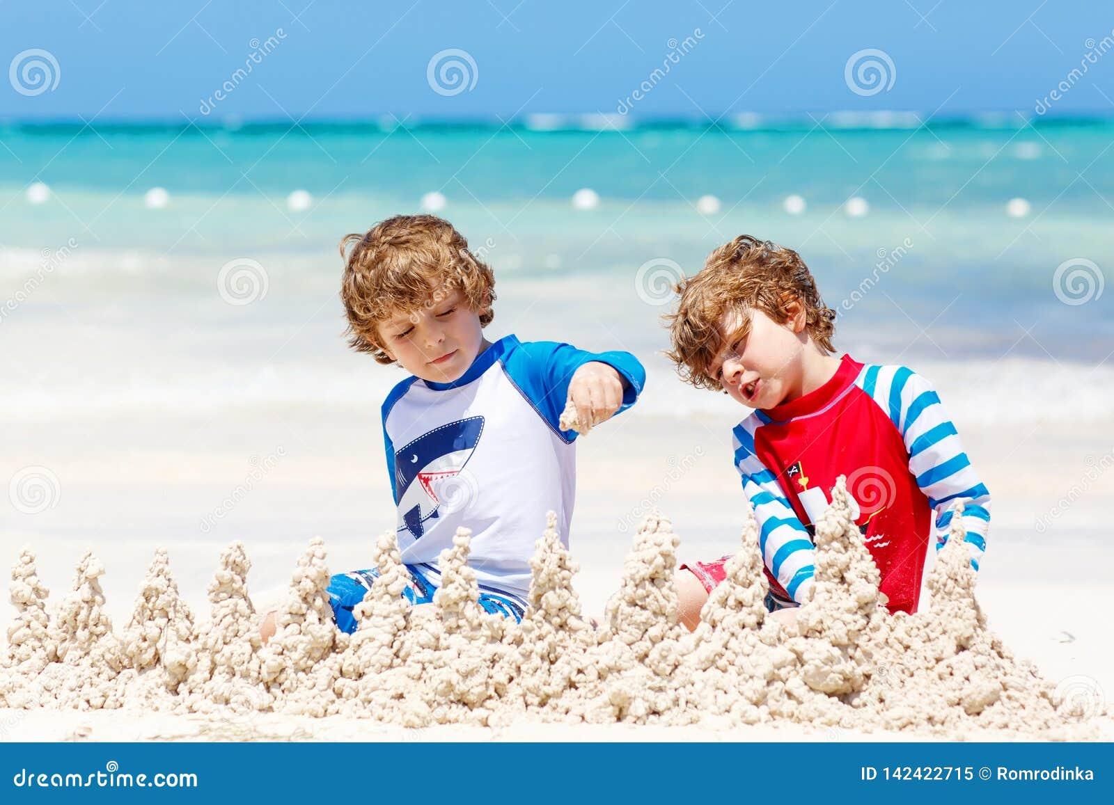 Två pojkar för små ungar som har gyckel med byggande av en sandslott på den tropiska stranden av den carribean ön leka för barn