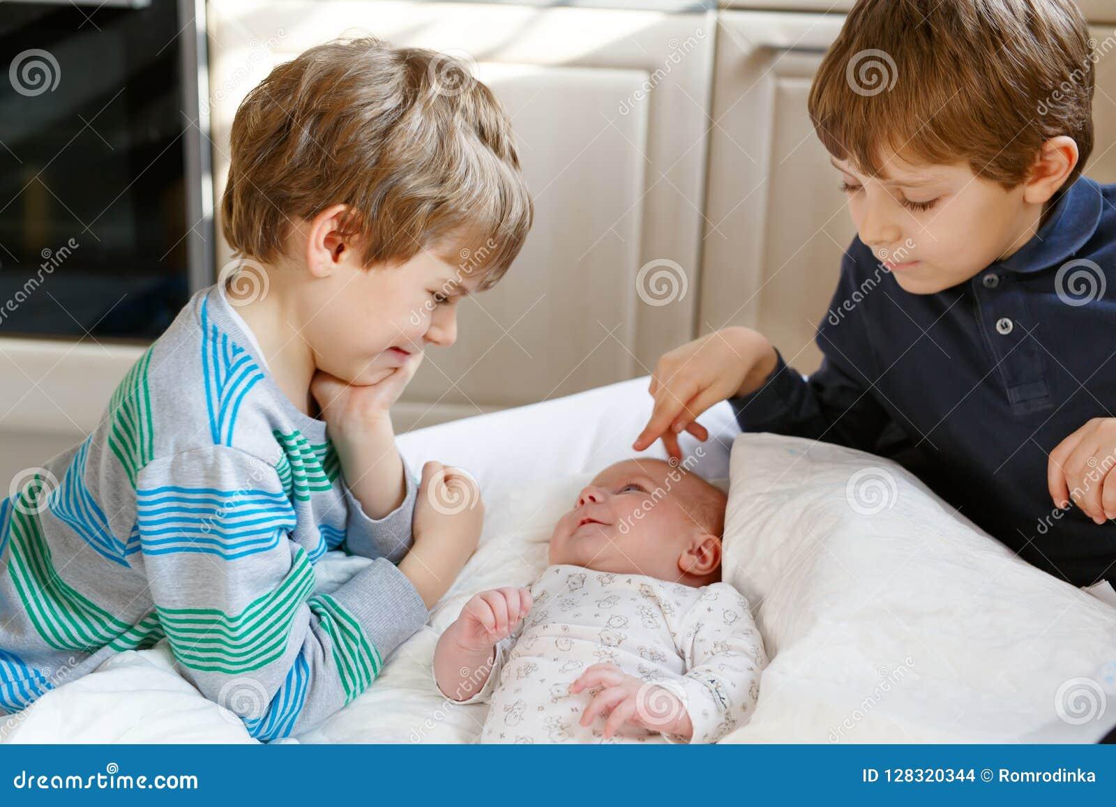 Två pojkar för små ungar som spelar med nyfött, behandla som ett barn systerflickan