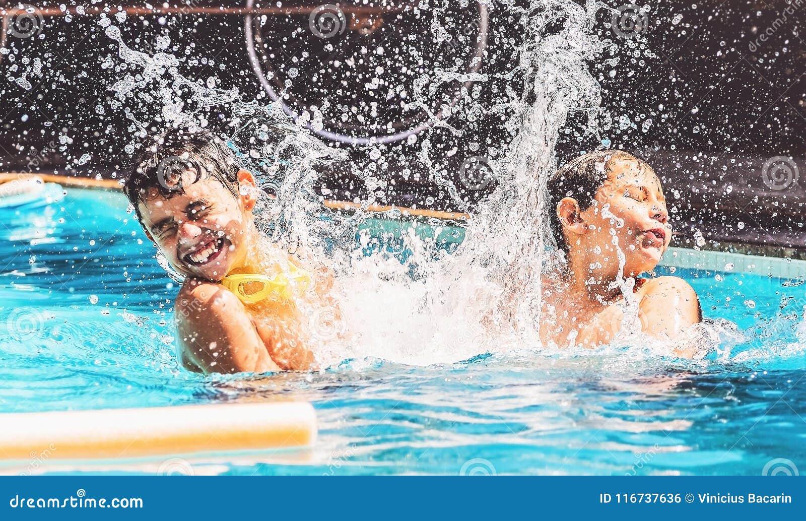 Två pojkar på den plaskande vatten- och hagyckeln för simbassäng