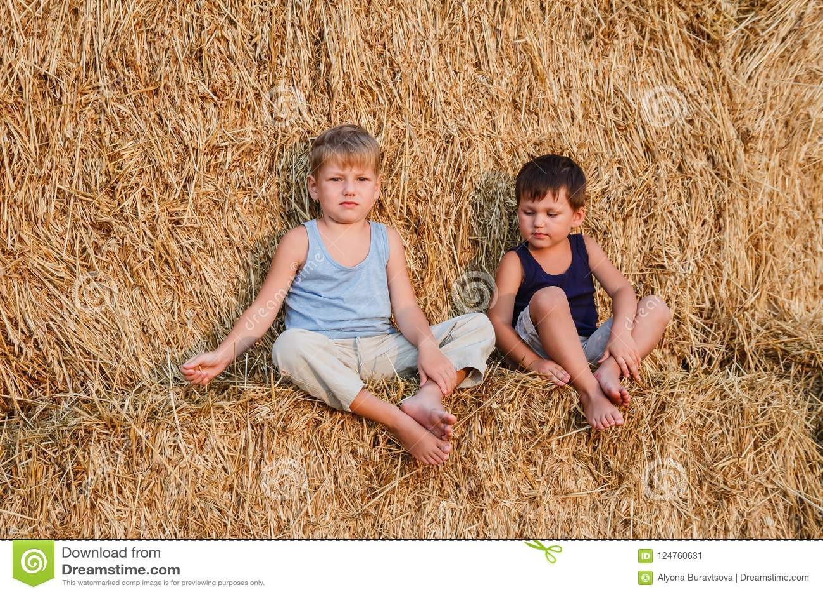 Två pojkar sitter på den stora ladugården