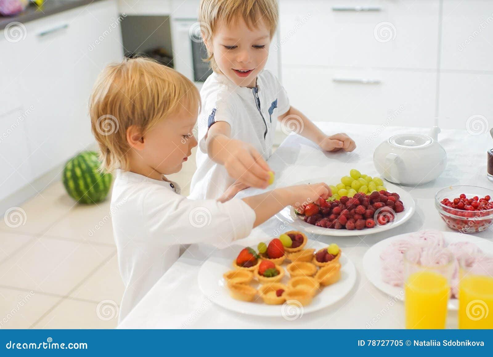 Två pojkar som förbereder frukosten i vitt kök
