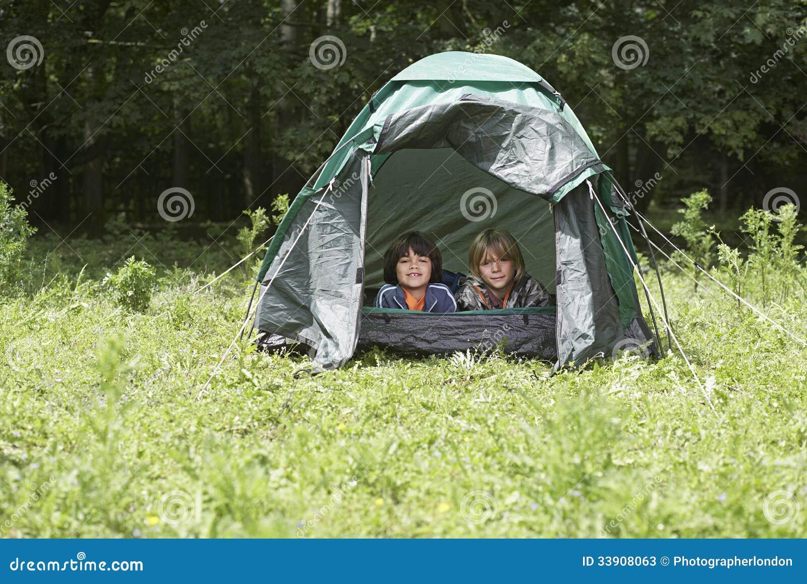 Två pojkar som ligger i tält