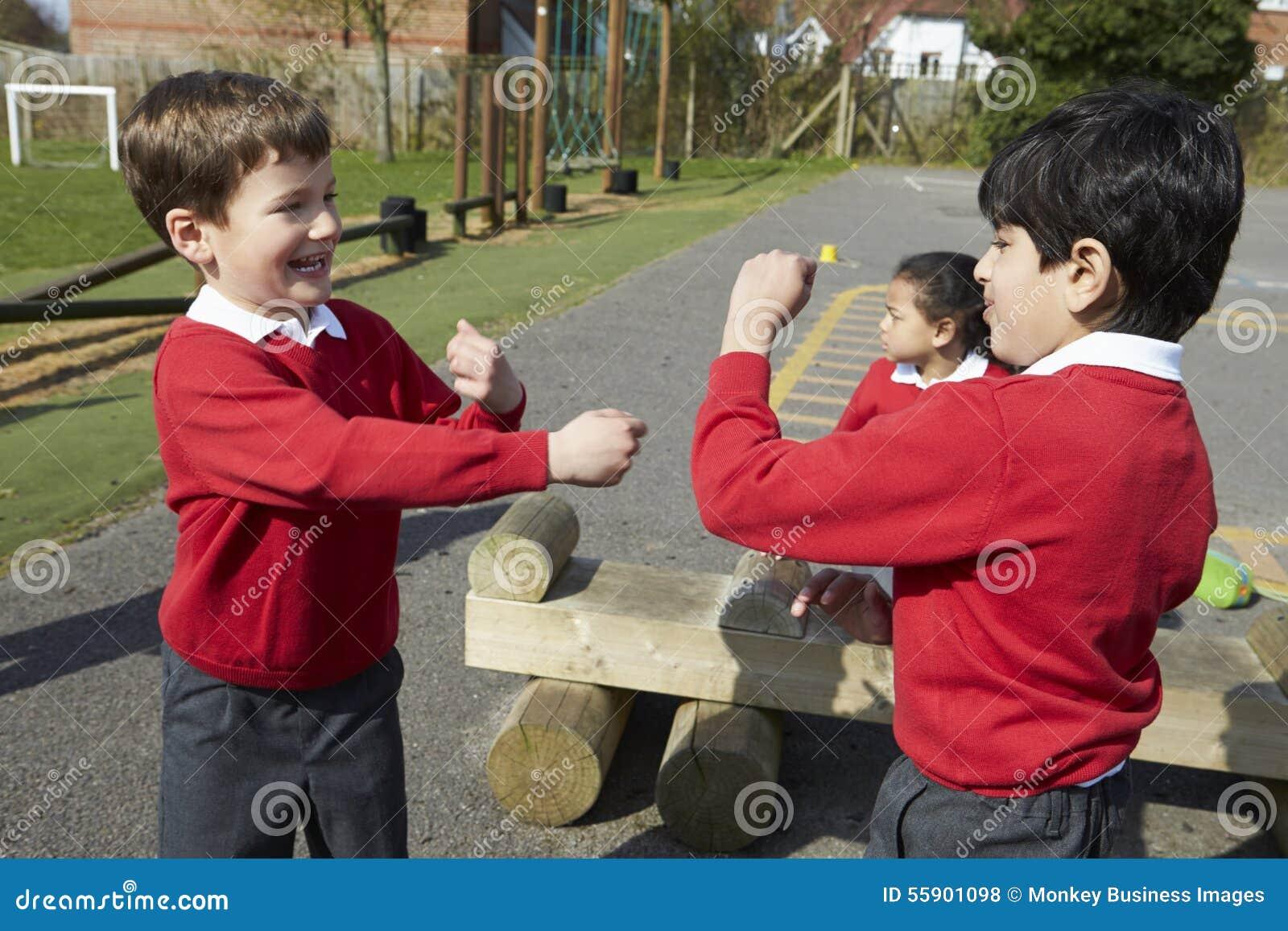 Två pojkar som slåss i skolalekplats