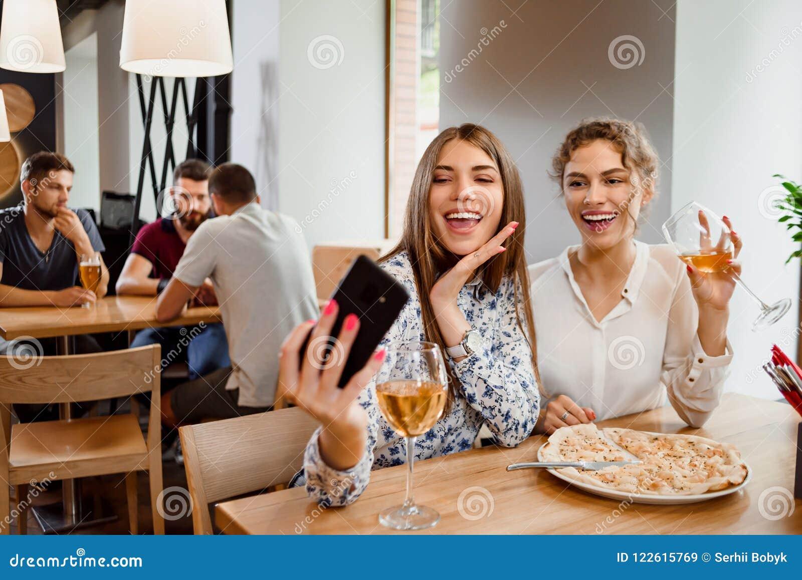 Två positiva flickor som ler och gör selfie med vin i restaurang